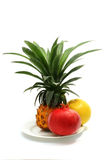 Pineapple, pomegranate, grapefruit on dish. Pineapple, pomegranate and grapefruit on white dish Royalty Free Stock Photography