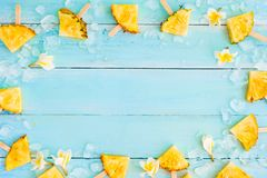 Pineapple popsicle sticks with ice on wood plank blue color. Frame layout summer fruit backgrond concept, top view stock images