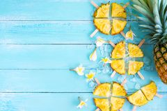 Pineapple popsicle sticks with ice on wood plank blue color. Summer fruit concept, top view royalty free stock images