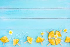 Pineapple popsicle sticks with ice on wood plank blue color. Summer fruit concept, top view royalty free stock image