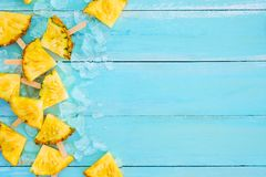 Pineapple popsicle sticks with ice on wood plank blue color. Summer fruit backgrond concept, top view, copy space royalty free stock photos