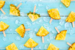 Pineapple popsicle sticks with ice on wood plank blue color. Summer fruit backgrond concept, top view, pattern stock image