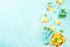 Pineapple popsicle sticks. Slice pineapple popsicle sticks and mint leaves, on light blue background with ice, flat lay summer concept, copy space top view stock photo