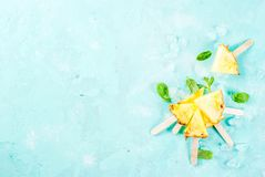 Pineapple popsicle sticks. Slice pineapple popsicle sticks and mint leaves, on light blue background with ice, summer concept, copy space flat lay top view stock photo