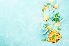 Pineapple popsicle sticks. Slice pineapple popsicle sticks and mint leaves, on light blue background with ice, flat lay summer concept, copy space top view royalty free stock images