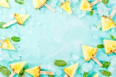Pineapple popsicle sticks. Slice pineapple popsicle sticks and mint leaves, on light blue background with ice, summer concept, copy space flat lay top view frame stock photos
