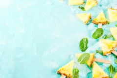 Pineapple popsicle sticks. Slice pineapple popsicle sticks and mint leaves, on light blue background with ice, summer concept, copy space royalty free stock image