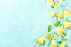 Pineapple popsicle sticks. Slice pineapple popsicle sticks and mint leaves, on light blue background with ice, summer concept, copy space flat lay top view royalty free stock photography