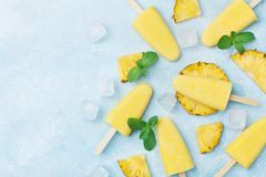 Pineapple popsicles or homemade ice cream top view. Summer refreshing food. Frozen fruit pulp. Pineapple popsicles or homemade ice cream from above. Summer Stock Photos