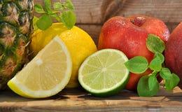 Pineapple, red apples, lemons Stock Photography