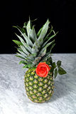 Pineapple with red roses on a marble table Stock Photo