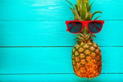 Pineapple with red sunglasses on a blue wooden background. Top view stock photo