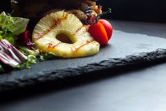 Pineapple ring lies on a black slate surface, in the background a hamburger. Royalty Free Stock Photo