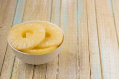 Pineapple rings in a white bowl. Canned ananas slices, copy spac Stock Photo