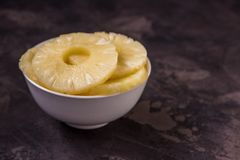 Pineapple rings in a white bowl. Canned ananas slices, copy spac Stock Image