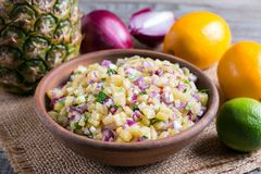 Pineapple salsa in a ceramic bowl on a table. Pineapple salsa in a ceramic bowl on a wooden table stock image
