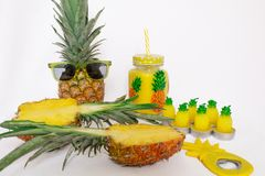 Pineapple set Two pineapples in sunglasses, a mug with juice, one pineapple, a can opener and candles in the shape of pineapples. On a white background. Still royalty free stock photo