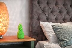 Pineapple shaped candle and lamp on bedside table. In room Royalty Free Stock Photography
