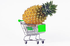 Pineapple and shopping cart Stock Images
