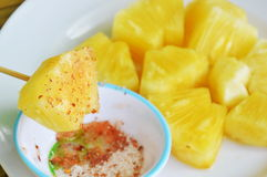 Pineapple slice dipping with mixed sugar salt and pepper on wooden stick Royalty Free Stock Photos