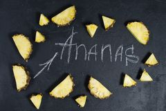 Pineapple slices on black background with space for text and chalk inscription. stock photo
