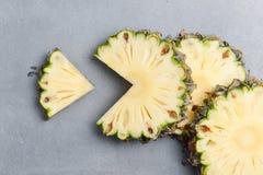 Pineapple slices  on dark rock. Background Stock Photos