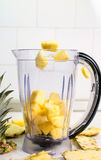 Pineapple slices falling into blender Royalty Free Stock Photography