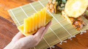 Pineapple with slices. Human female hands holding pineapple slices. Tropical fruit concept. Close-up, Selective focus Stock Photography