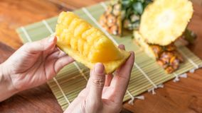 Pineapple with slices. Human female hands holding pineapple slices. Tropical fruit concept. Close-up, Selective focus Stock Photo