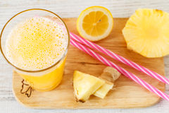 Pineapple slices and juice in glassware on wooden table Stock Images