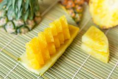Pineapple with slices. Fresh of pineapple slices Asian-style on the bamboo place mats background. Tropical fruit concept. Selective focus Royalty Free Stock Photos