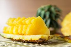 Pineapple with slices. Fresh of pineapple slices Asian-style on the bamboo place mats background. Tropical fruit concept. Selective focus Stock Photo