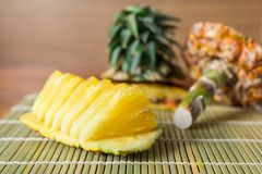 Pineapple with slices. Fresh of pineapple slices Asian-style on the bamboo place mats background. Tropical fruit concept. Selective focus Royalty Free Stock Images