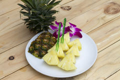 Pineapple slices on the white dish on the wood. Pineapple slices in the white dish on the wood Stock Image