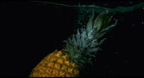 Pineapple in slow motion falling in the water stock footage