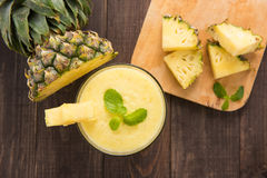 Pineapple smoothie with fresh pineapple on wooden table.  Royalty Free Stock Images