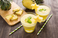 Pineapple smoothie with fresh pineapple on wooden table.  Stock Image