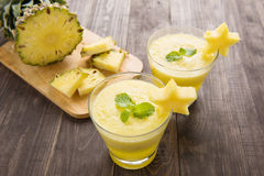 Pineapple smoothie with fresh pineapple on wooden table.  Stock Photo
