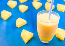 Pineapple smoothie with fresh pineapple on wooden blue table stock images