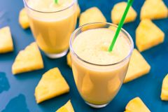 Pineapple smoothie with fresh pineapple on wooden blue table. stock photography