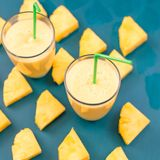 Pineapple smoothie with fresh pineapple on wooden blue table. stock images