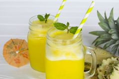 Pineapple smoothie juice yellow drink in the morning healthy on white wood background. stock photo