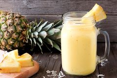 Pineapple smoothie in a mason jar, scene against wood Royalty Free Stock Images