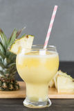 Pineapple smoothie on wood Royalty Free Stock Images