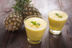 Pineapple smoothie on wooden table Royalty Free Stock Photos