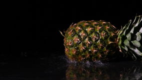 Pineapple spinning and falling on wet black surface stock video