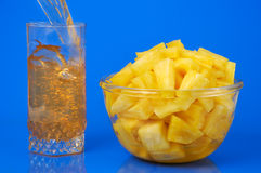 Pineapple still-life. Pineapple pieces in bowl and glass filling with juice isolated on blue background royalty free stock photo
