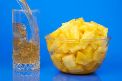 Pineapple still-life. Pineapple pieces in bowl and glass filling with juice isolated on blue background royalty free stock photos