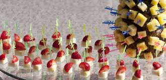 Pineapple and strawberries on skewers. Table appointments outdoors royalty free stock photo