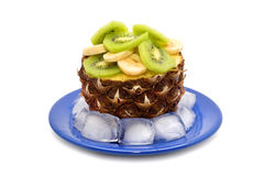 Pineapple stuffed with chopped banana and kiwi on a blue plate with ice cubes Royalty Free Stock Image